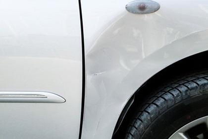 少し凹んだ白い車