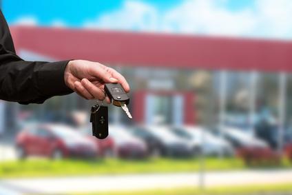 車の販売店の前でキーを持つ人