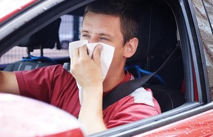 鼻をティッシュで覆う男性