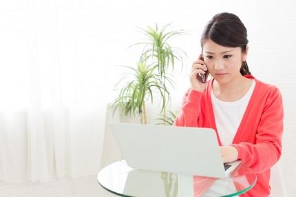 PCを見ながら電話をする女性