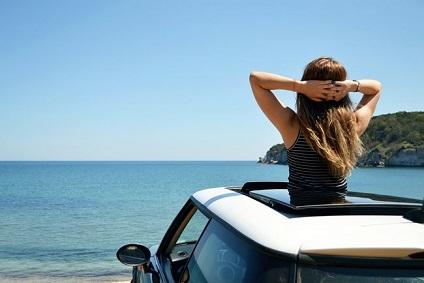 ルーフキャリアから海を眺める女性