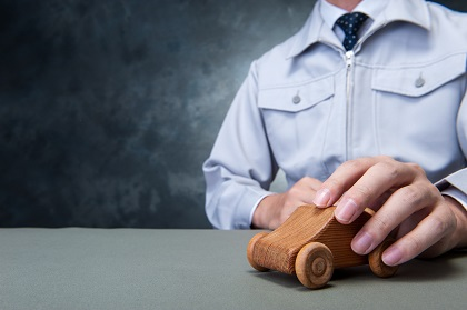 木製おもちゃの車を動かす男性