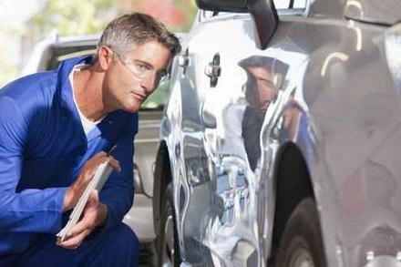 車のへこみを見る整備士