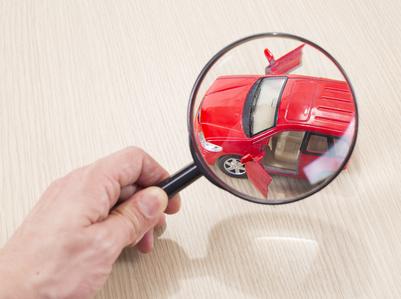 赤い色の車を虫眼鏡で見る