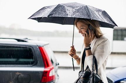 傘をさす女性と車