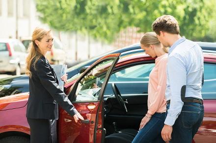 車を見る男女とお店の女性