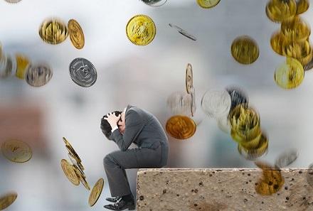 落ちてくる硬貨の中にいる頭を抱える男性