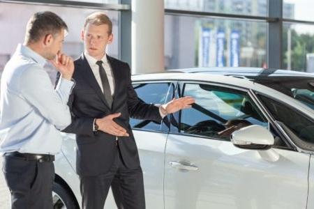 白い車とディーラーの営業マン