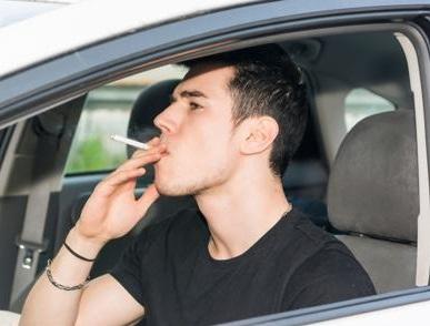車でタバコを吸う男性