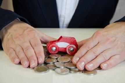 小銭とミニカーを手で包み込む