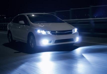 ヘッドランプ点灯の白い車