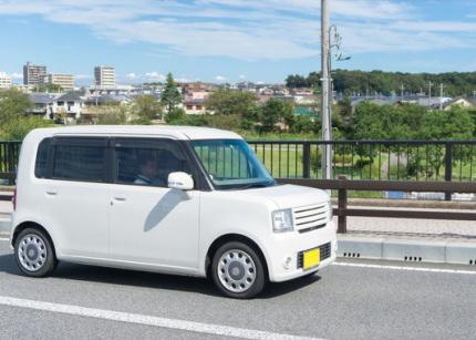 公道を走る白い軽自動車