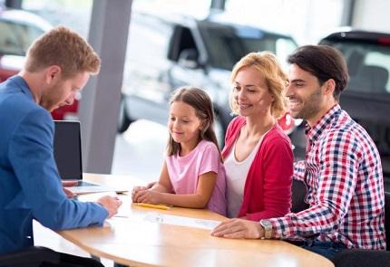 話合いをする家族と車ディーラー担当者