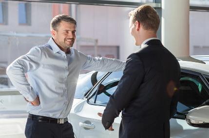 車の前で話をする男性2人