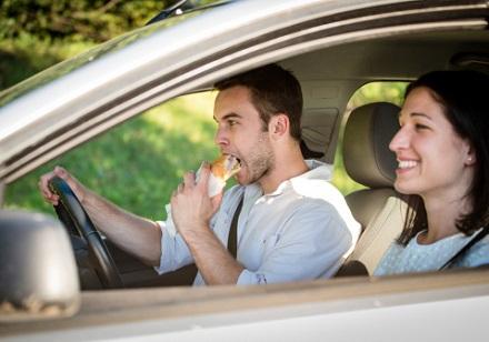 運転しながらパンを食べる男性