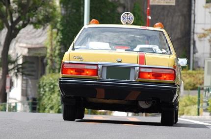 公道を走る黄色のタクシー