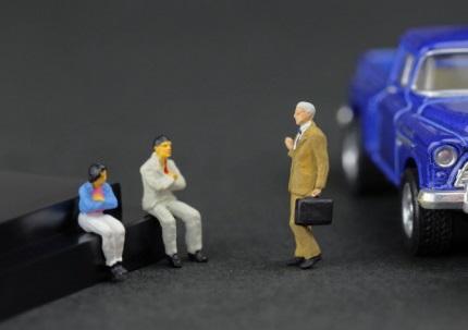 青い車の傍で話をする人たち