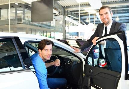 試乗車に乗る男性と営業マン