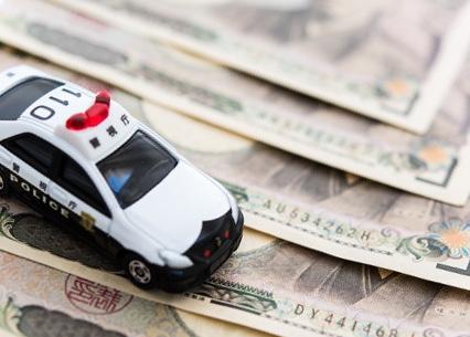 一万円札の上に乗るパトカーのおもちゃ