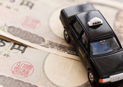 黒いミニカーのタクシーと一万円札