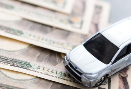 一万円札とシルバーのミニカー