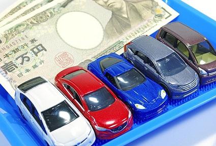 一万円札と複数のミニカー