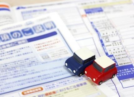 赤と青の2台のミニカーと保険資料