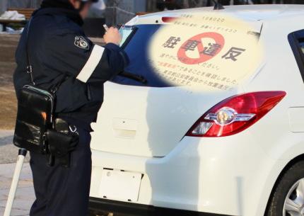 白い車の駐車違反を取り締まる警察官