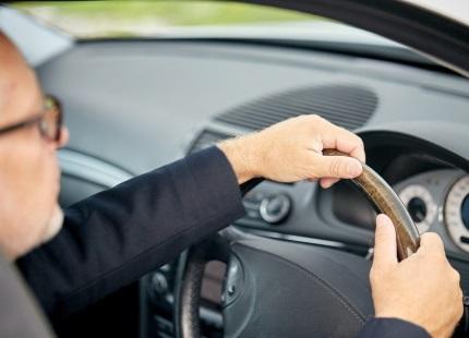 車を運転するメガネをかけた男性