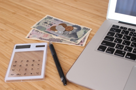 パソコンと電卓とお札