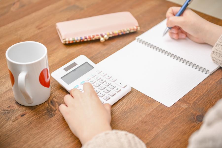 管理費用を電卓で計算している女性