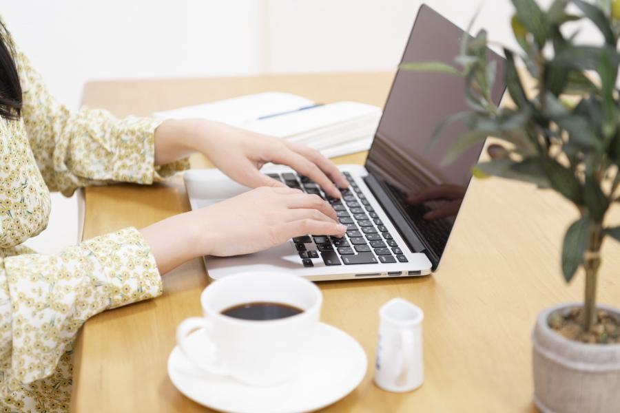 ノートパソコンでホームページを見る女性